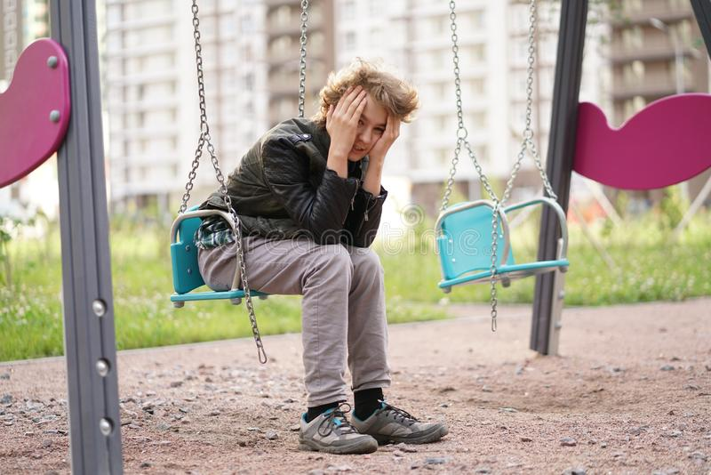 Cute positive boy teenager on the Playground in the city alone royalty free stock image