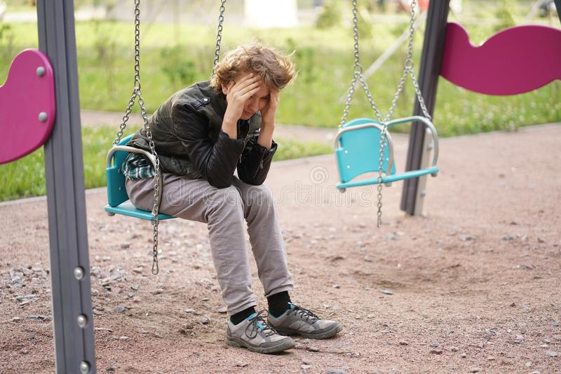 Cute positive boy teenager on the Playground in the city alone royalty free stock photography