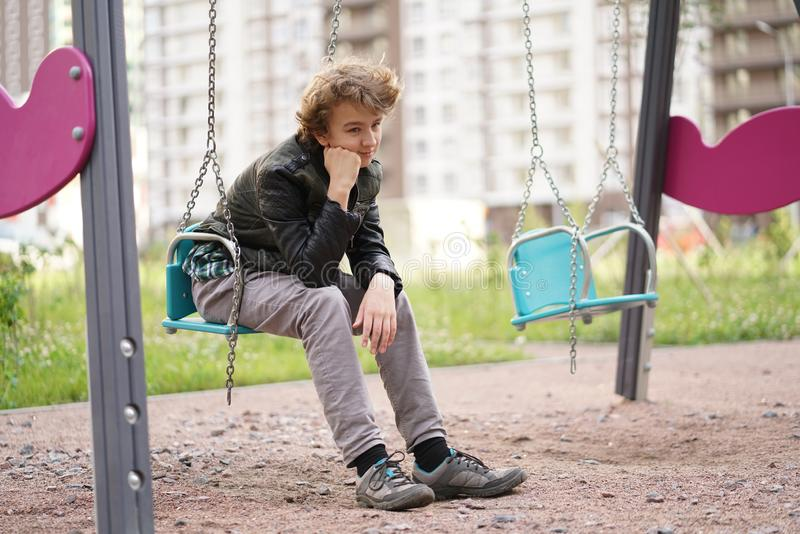 Cute positive boy teenager on the Playground in the city alone royalty free stock images