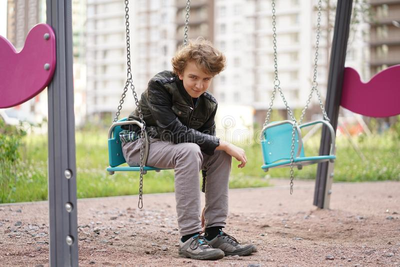 Cute positive boy teenager on the Playground in the city alone stock photography