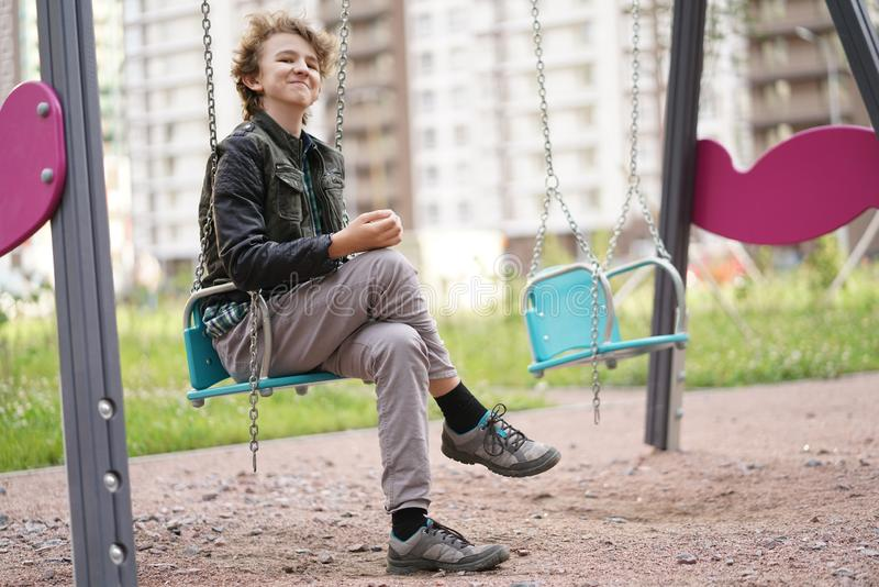 Cute positive boy teenager on the Playground in the city alone stock photos