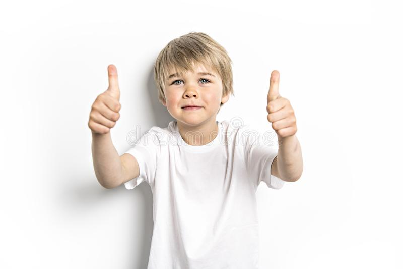 A cute positive five year old boy studio portrait on white background royalty free stock images