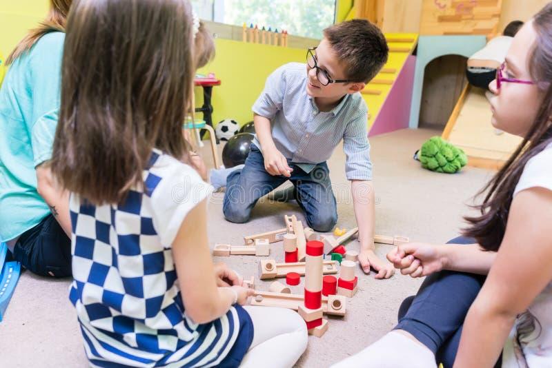 Pre-school boy cooperating with kids under guidance of kindergarten teacher stock image