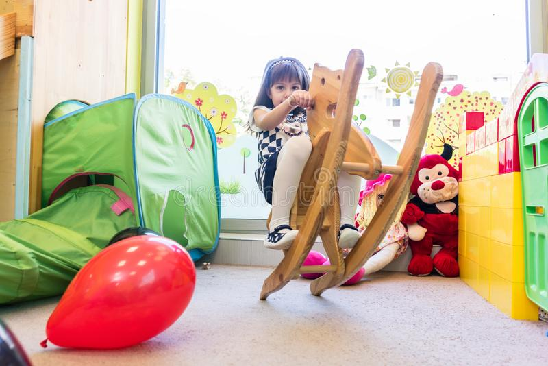 Cute pre-school girl swinging on a vintage wooden horse stock photo