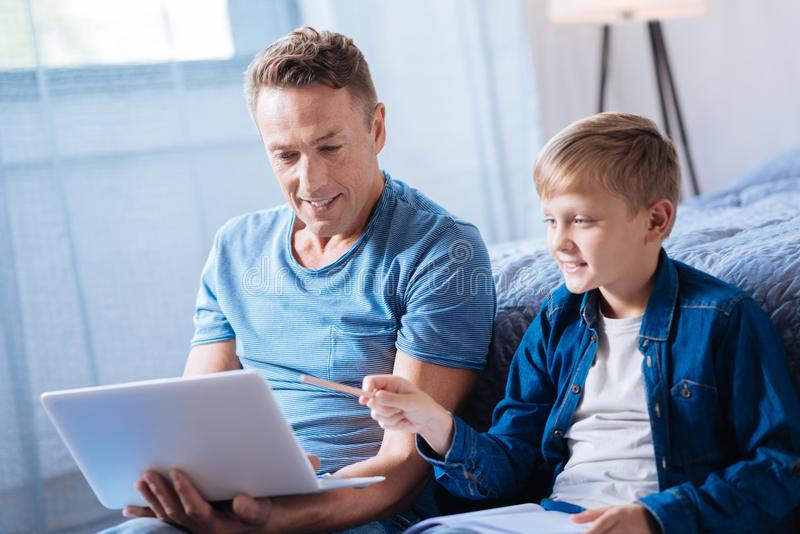 Cute pre-teen boy discussing presentation with his father royalty free stock image