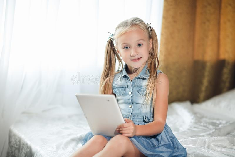 Cute pre teenager girl doing homework lying on bed at home. Young pretty girl wearing denim sundress studying online with tablet, stock image