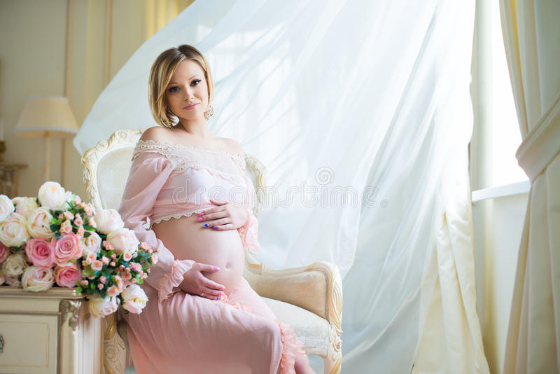 Cute pregnant woman sitting on chair near billowing curtains and hugs belly with love stock images