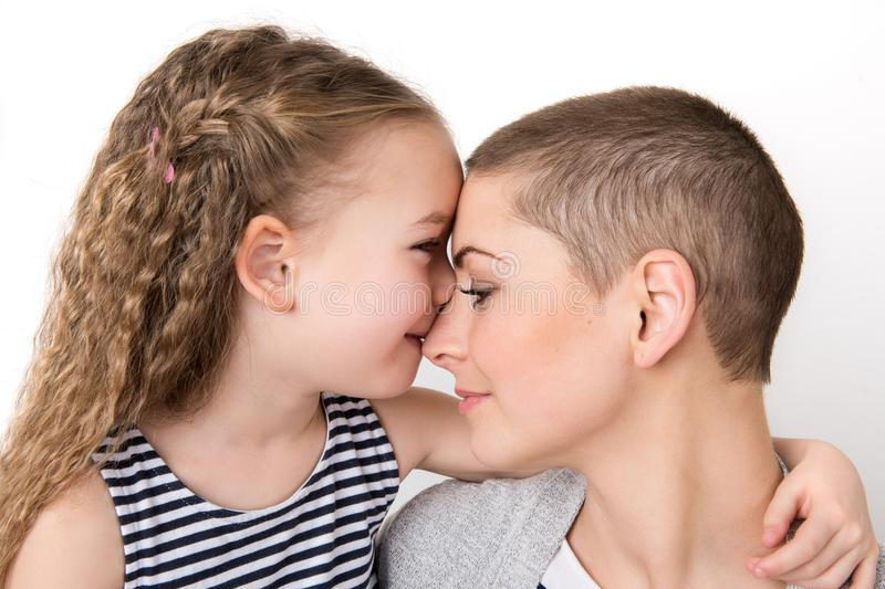 Cute preschool age girl with her mother, young cancer patient in remission. Cancer patient and family support. stock photos