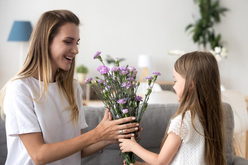 Cute preschool daughter giving to mother flowers stock photo