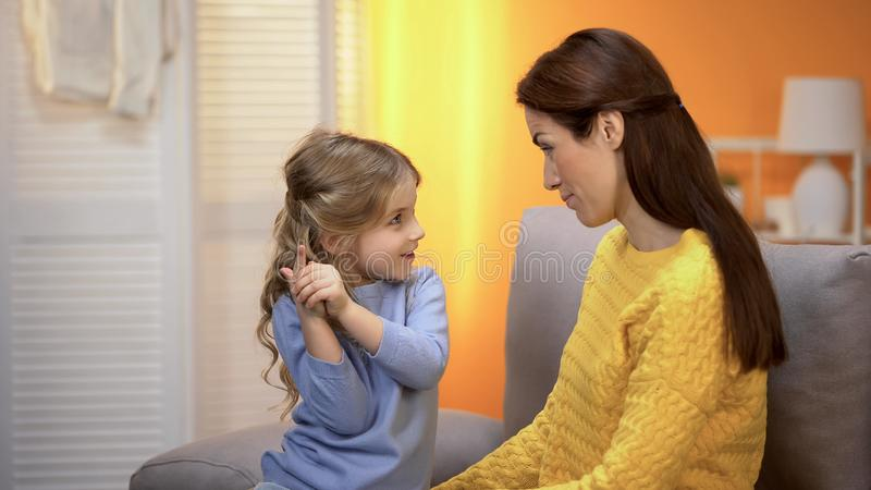 Cute preschool girl telling happy mommy funny stories and laughing, having fun royalty free stock images