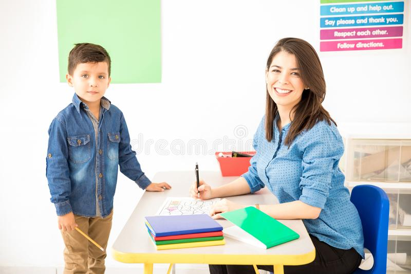Cute preschool teacher grading student`s work. Attractive Hispanic preschool teacher grading a student`s work while sitting on her desk in a classroom stock images