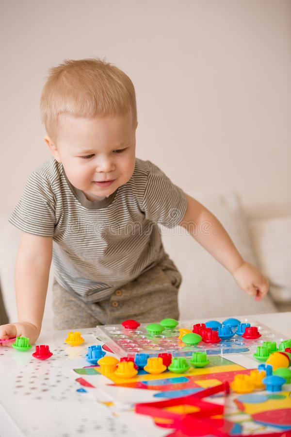 Cute preschooler child boy plays with mosaic at home. A blond little toddler playing in kid`s room. Leisure activities. Indoors. Boy sorting colorful children` stock photography