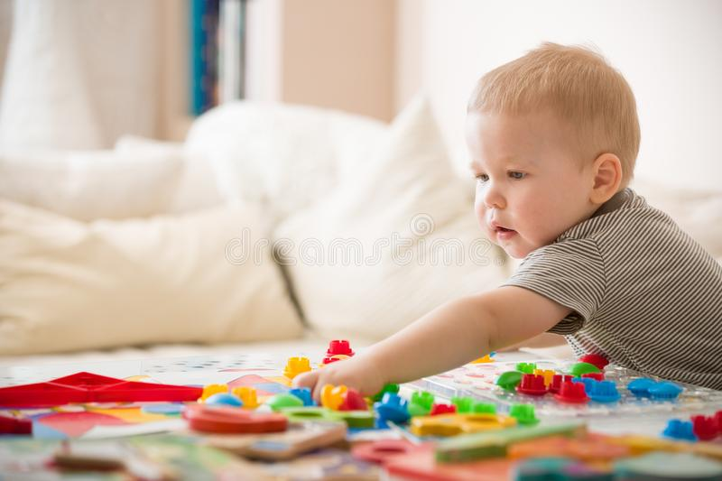 Cute preschooler child boy plays with mosaic at home. A blond little toddler playing in kid`s room. Leisure activities. Indoors. Boy sorting colorful children` royalty free stock photo
