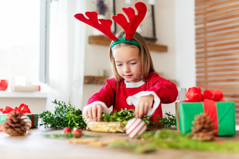 Cute preschooler girl dressed in reindeer costume wearing reindeer antlers making christmas wreath in living room. Christmas decoration family fun concept stock photos