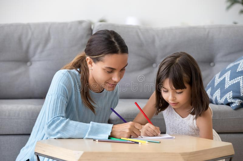 Preschooler girl entertain drawing picture with young mom royalty free stock photo