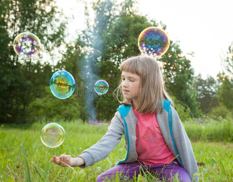 Cute preschooler girl playing with soap bubbles stock photos