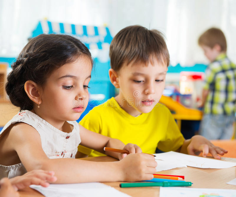 Cute preschoolers drawing with colorful pencils stock image