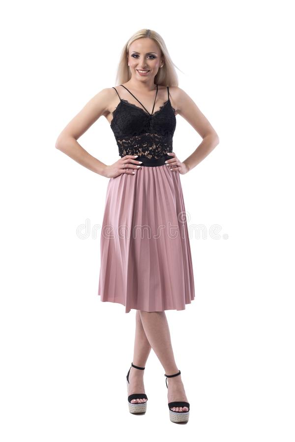 Cute pretty blonde woman in black lace top and salmon color skirt posing with arms on hips. Full body isolated on white background royalty free stock photos