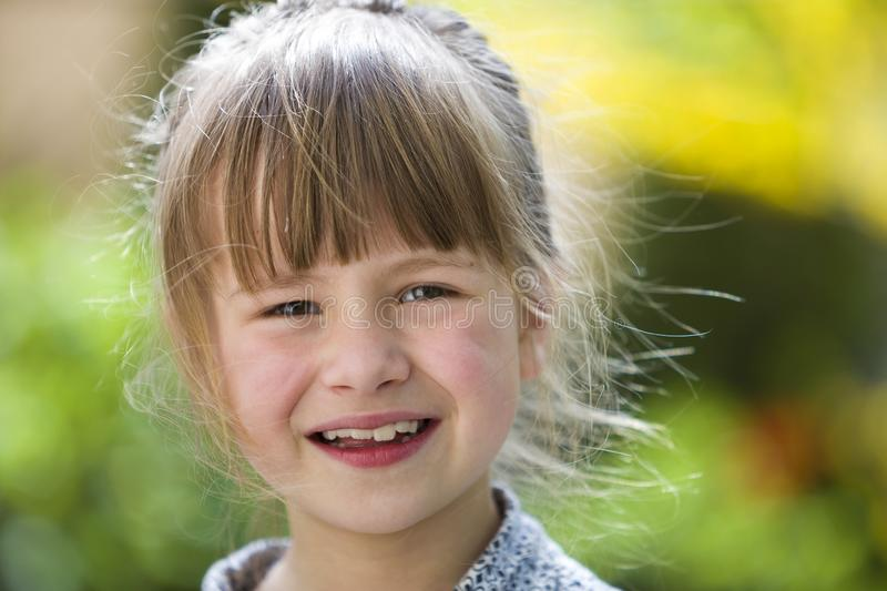 Cute pretty child girl with gray eyes and fair hair smiling in camera outdoors on blurred sunny green and yellow bright bokeh royalty free stock photography