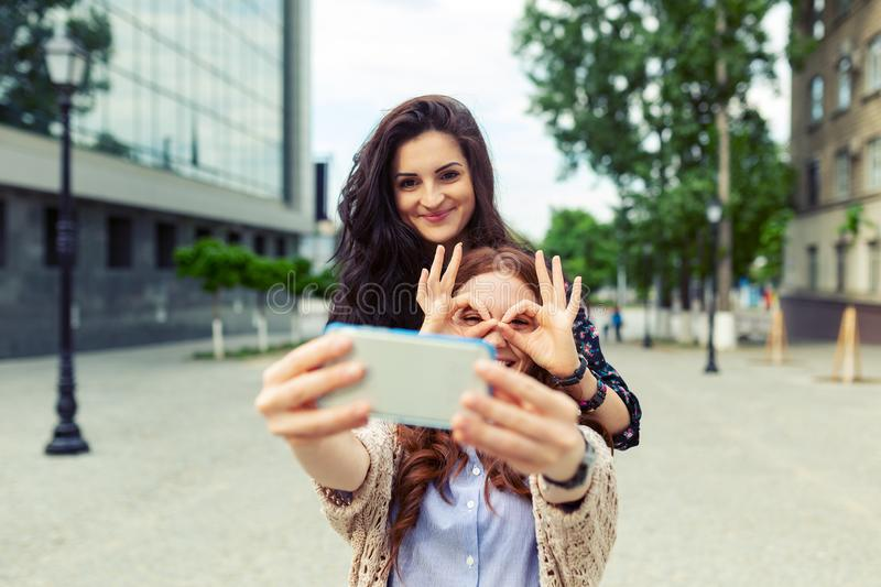 Two girls making funny selfie on the street, having fun together stock image