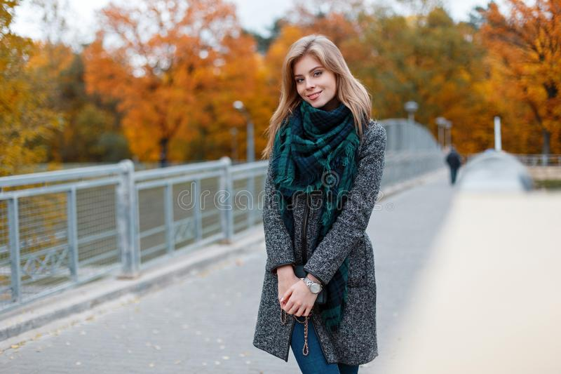 Cute pretty happy young woman in an elegant coat in a vintage checkered green scarf in jeans stands on a bridge in the park stock photos