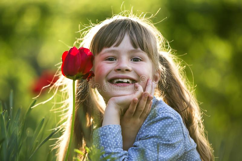 Cute pretty smiling child girl with gray eyes and long hair with bright red tulip flower on blurred sunny green bokeh background. royalty free stock photos