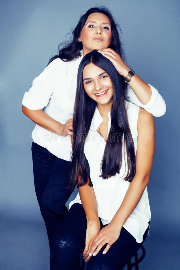 Cute pretty teen daughter with mature mother hugging, fashion style brunette, lifestyle people concept close up. Cute pretty teen daughter with mature mother royalty free stock photo