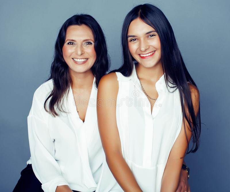 Cute pretty teen daughter with mature mother hugging, fashion style brunette, lifestyle people concept close up. Cute pretty teen daughter with mature mother royalty free stock image
