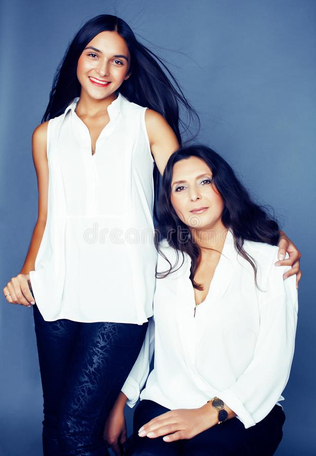 Cute pretty teen daughter with mature mother hugging, fashion style brunette, lifestyle people concept close up. Cute pretty teen daughter with mature mother stock images