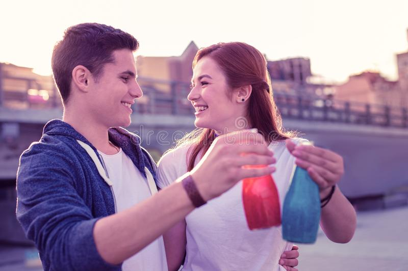 Cute pretty young guys hugging each other and drinking juices. Happy young couple. Cute pretty young guys hugging each other and drinking juices from little stock image