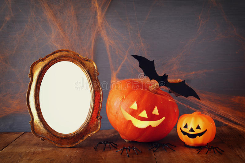 Cute pumpkin next to blank photo frame on wooden table royalty free stock images
