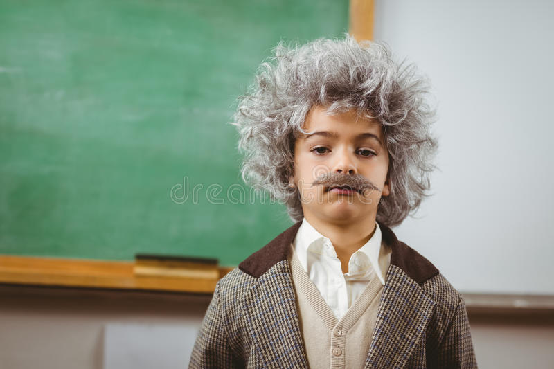 Cute pupil dressed up like Einstein in a classroom royalty free stock images