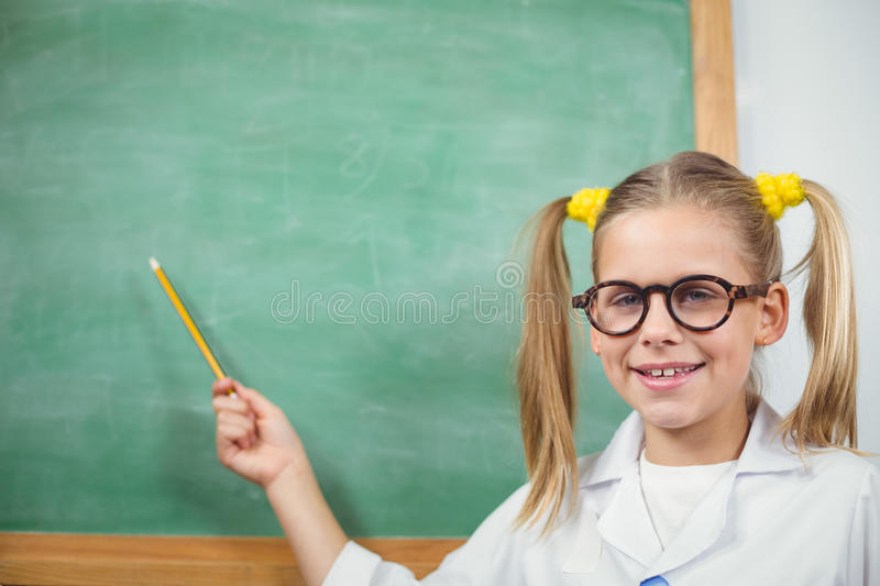Cute pupil with lab coat pointing on chalkboard stock image
