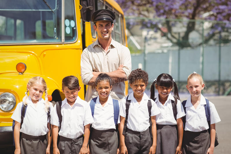 Cute pupils with their school bus driver. Outside the elementary school royalty free stock photography