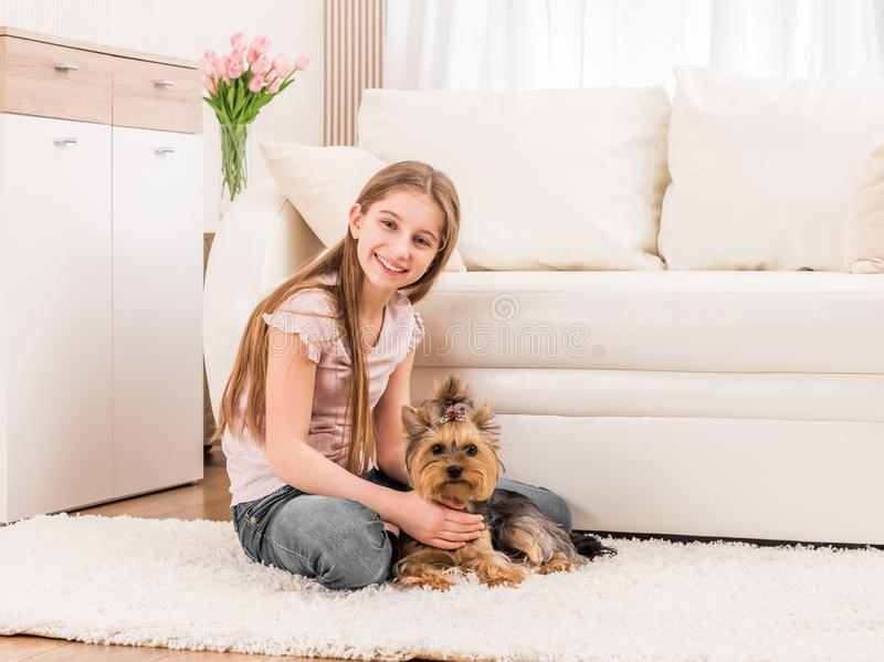 Cute puppy and happy young girl. Playing in the living room royalty free stock images