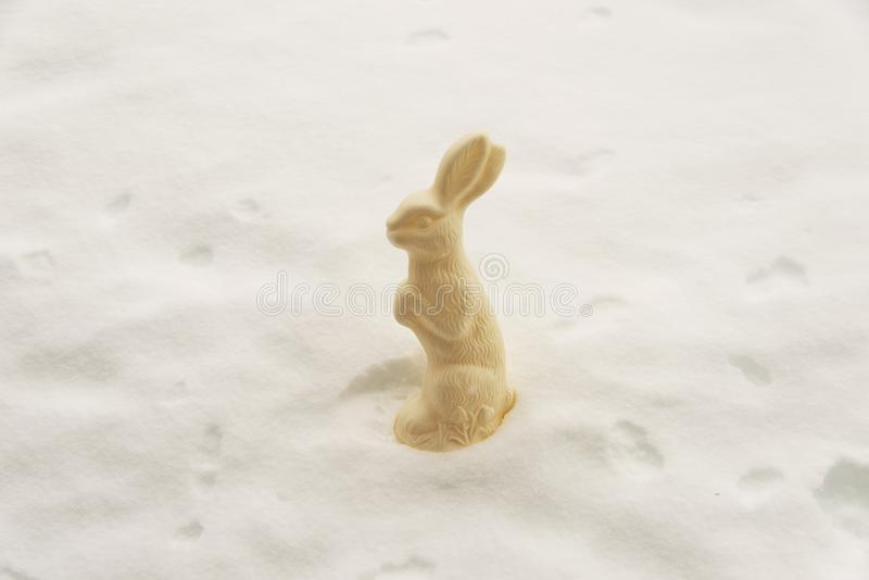 A cute rabbit shaped chocolate in the white snow as an abstract still life royalty free stock photo