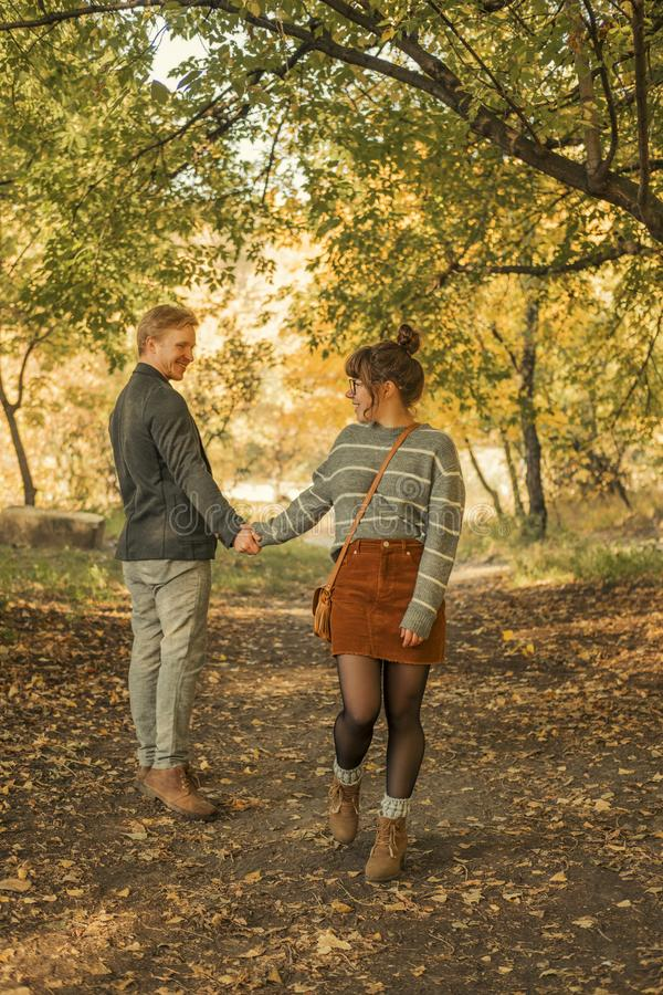 Cute red haired couple of man and woman in casual outfit on a date. They walking in autumn park smiling, hugging and having fun. Cute red haired couple of men stock image