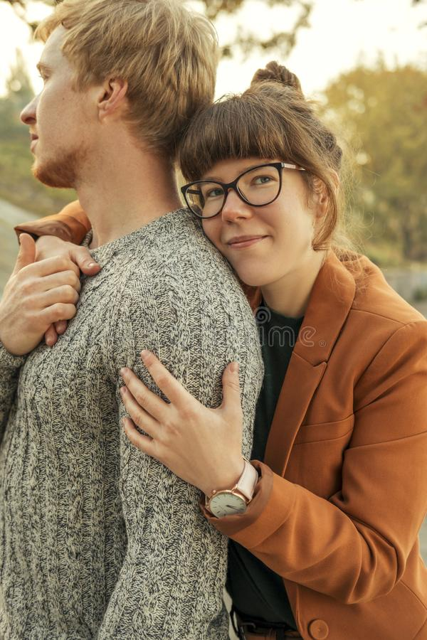 Cute red haired couple of man and woman in casual outfit on a date. They walking in autumn park smiling, hugging and having fun. Cute red haired couple of men royalty free stock photography