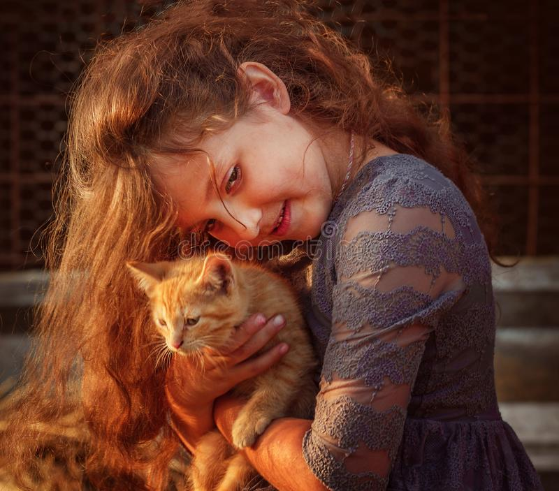 Cute girl with a red kitten. stock photos