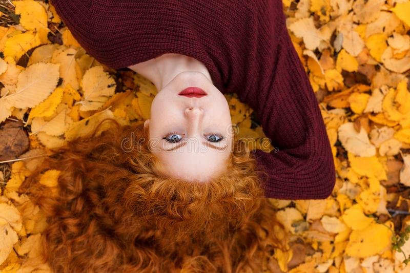 Cute red-haired girl lying on yellow leaves royalty free stock photos