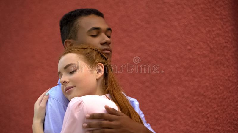 Cute red-haired girl snuggling to her mixed-race boyfriend, couple hugging. Stock photo royalty free stock photo