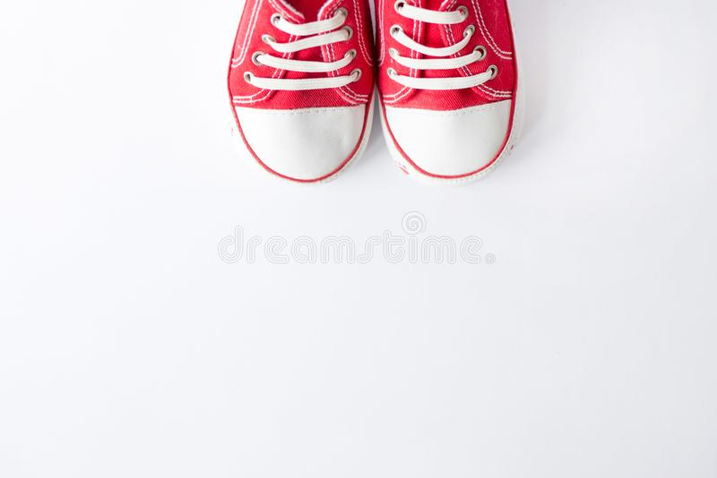 Cute red small sized canvas shoes top view on white background with copyspace stock photography
