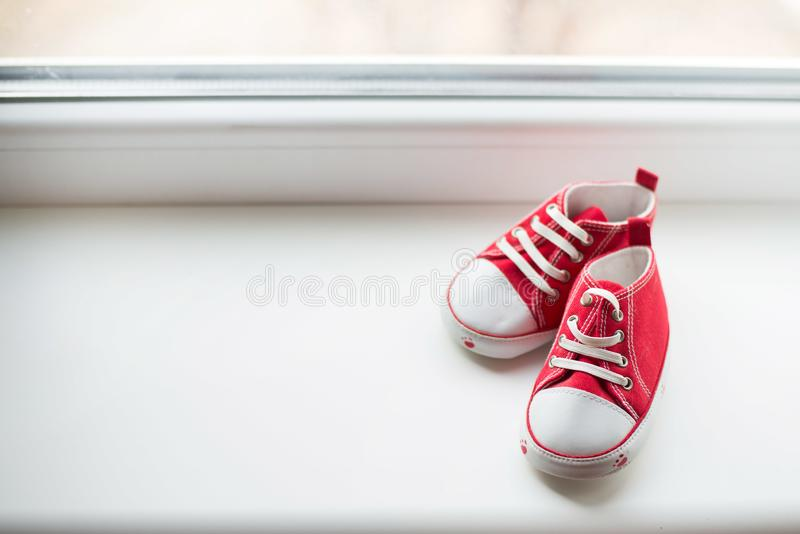 Cute red small sized canvas shoes top view on white background with copyspace royalty free stock photo