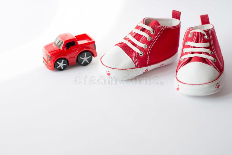 Cute red small sized canvas shoes with toy car top view on white background . copyspace royalty free stock image