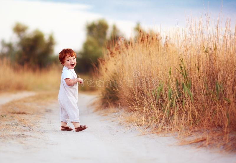 Cute redhead baby toddler walking along the summer path stock images