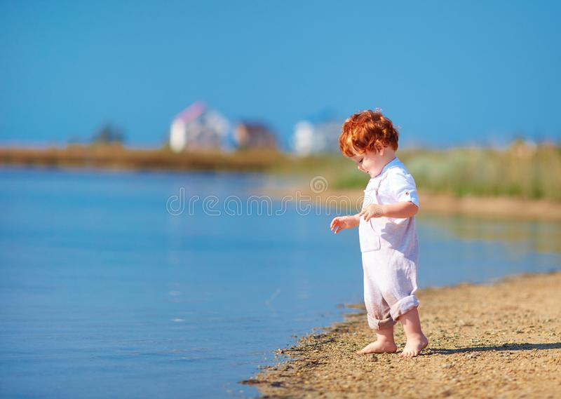 Cute redhead toddler baby boy walking at lake coast in the summer morning. Cute happy redhead toddler baby boy walking at lake coast in the summer morning stock photography