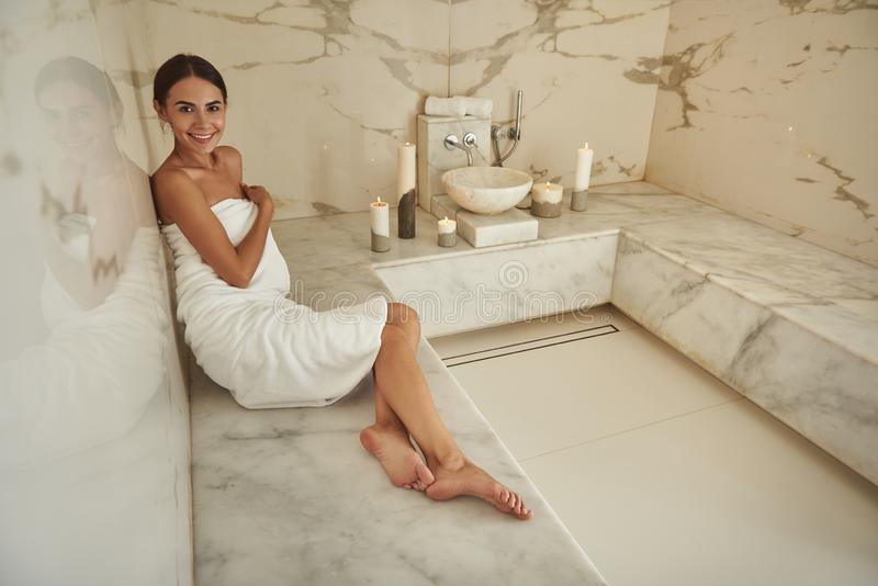 Pretty lady wearing white towel and looking happy in Turkish bath royalty free stock photo