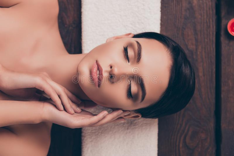 Cute relaxed young woman laying in spa salon with closed eyes royalty free stock photos