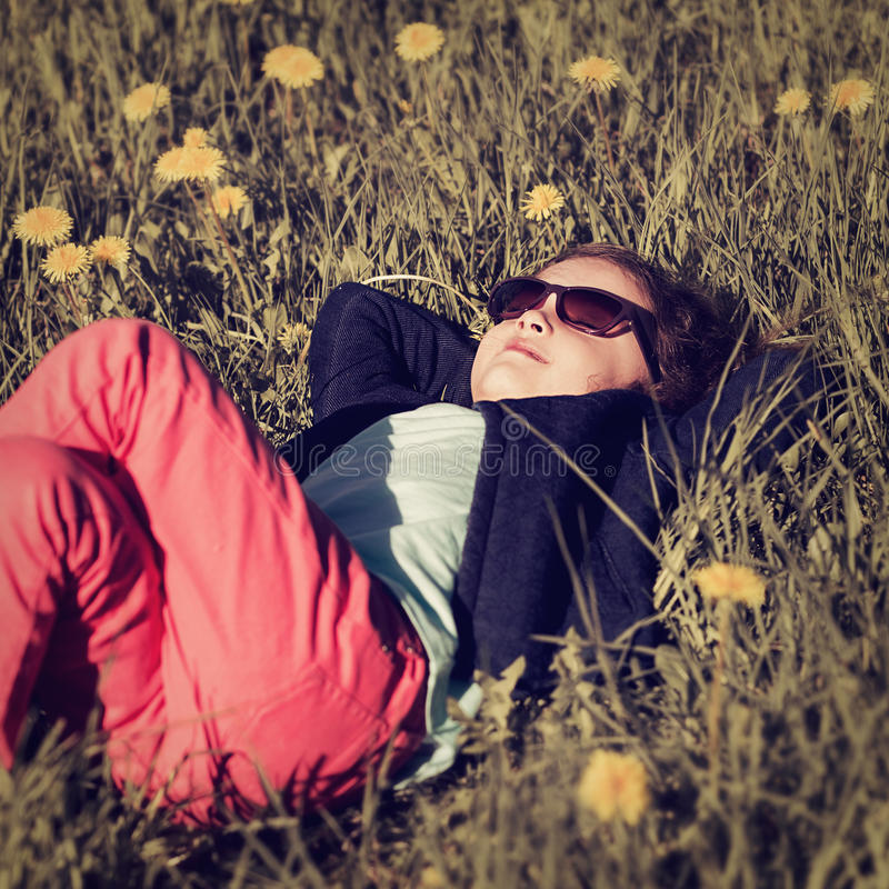 Cute relaxing kid girl in fashion clothers and sunglasses lying. In green grass with yellow flowers royalty free stock photos