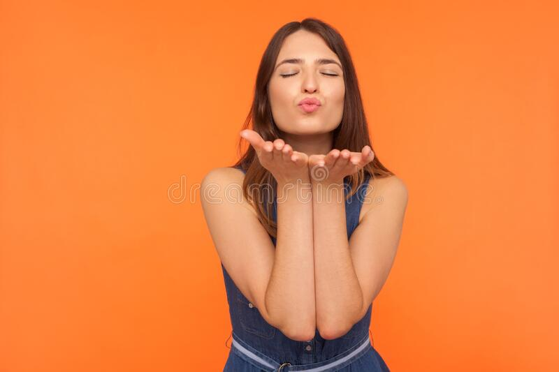 Cute romantic brunette woman standing with palms up and closed eyes in pleasure, sending amorous air kiss. To camera, demonstrating affection, love. indoor royalty free stock photography